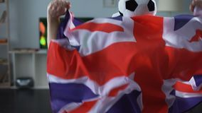 供以人员在家拿着大英国旗子,在电视的支持者观看的橄榄球赛 股票视频