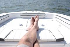 供以人员在小船的前面的腿 免版税库存图片