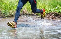 供以人员在山的赛跑,横渡小河 库存图片
