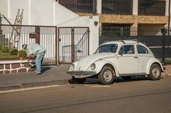 供以人员在房子前面的绘画篱芭有在它旁边停放的甲虫汽车的在São曼纽尔 免版税库存照片