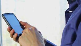 供以人员在接触电话,特写镜头的佩带的紫罗兰色衬衣键入的消息 股票录像