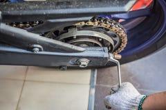 供以人员在摩托车的检查和调节摩托车链子 免版税图库摄影