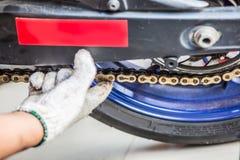 供以人员在摩托车的检查和调节摩托车链子 免版税库存图片