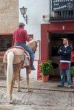 供以人员在朗达,西班牙街道上的骑乘马  免版税库存照片