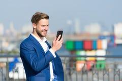 供以人员在正式衣服的微笑与室外的手机 与智能手机的愉快的商人在晴朗的大阳台 营业通讯和 免版税库存图片