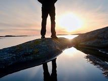 供以人员在水池反映的高起动的远足者腿,有日落太阳的海 在岩石的旅游图 图库摄影