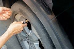 供以人员在汽车轮胎的填装的空气  接近的现有量 库存图片