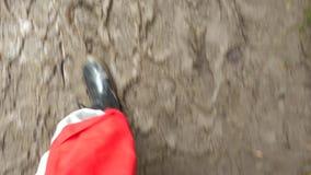 供以人员在泥泞的水坑的步在胶靴顶视图 在泥浆坑的腿在充分鞋子孔顶视图 影视素材
