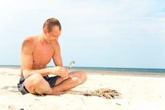 供以人员在海滩的尝试的轻的火与放大器 免版税库存图片