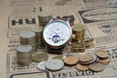 供以人员在皮带的` s腕子机械手表和在一张老报纸的金属硬币 库存图片