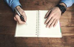 供以人员在笔记薄的文字在木书桌 库存图片