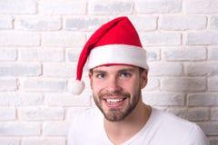 供以人员在红色圣诞老人帽子的微笑在白色砖墙上 免版税图库摄影