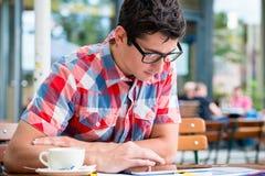 供以人员在街道咖啡馆读书的饮用的咖啡在片剂设备 免版税库存图片