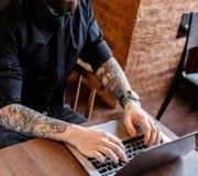 供以人员在键入木的桌上坐膝上型计算机 库存照片