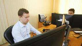 供以人员在键盘的类型在工作的同事附近坐计算机 影视素材