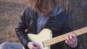 供以人员在领域的戏剧电吉他靠近树在日落 慢的行动 股票视频