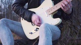 供以人员在领域的戏剧电吉他靠近树在日落 慢的行动 股票录像