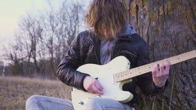 供以人员在领域的戏剧电吉他靠近树在日落 股票视频