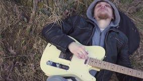 供以人员在领域的戏剧电吉他靠近树在日落 影视素材