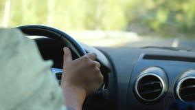 供以人员在驾驶在漫长的路的方向盘的` s手一辆汽车沿山 免版税库存图片