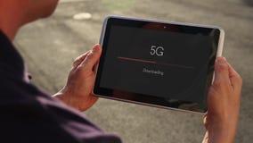 供以人员在5G的下载录影在片剂个人计算机