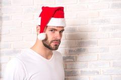 供以人员在T恤杉的圣诞老人在白色砖墙上 库存照片
