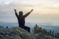 供以人员坐一个石山坡,看从高度的手看法并且享受自由 免版税图库摄影