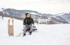 供以人员坐与木雪撬的山上面 免版税库存照片