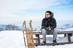 供以人员坐与木雪撬的山上面 免版税库存图片