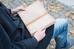 供以人员坐与被回收的纸被打开的空的笔记本  免版税库存图片