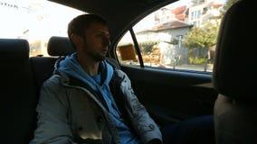 供以人员坐在汽车后座,看在窗口外面街道,出租汽车乘驾 股票视频