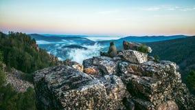 供以人员坐岩石在山上面和遇见日出,在深谷的重的薄雾的旅行家 库存照片