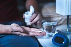 供以人员坐床采取安眠药或夜医学的  库存照片