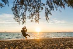 供以人员坐摇摆在海滩在与一条美丽的longtail小船的日出期间在海 泰国海滩假日 库存照片