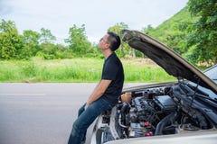 供以人员坐残破的汽车等待的协助 库存图片