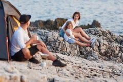 供以人员坐看他的妻子和女儿的岩石海岸,坐近 库存图片