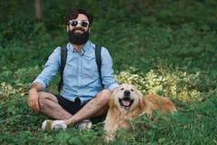 供以人员基于有他的狗的草开会盘的腿 图库摄影