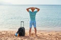 供以人员夏天衣裳的游人带着一个手提箱在他的手上,看海滩的海,时刻的概念旅行 免版税库存照片