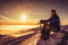 供以人员就座在山顶部,男性在单独一个山顶的远足者赞赏的冬天风景有冰斧的 免版税图库摄影
