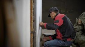供以人员工作在完成在墙壁上的内部和申请的灰泥 影视素材