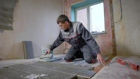 供以人员工作在建造场所和放置瓦片在地板上 股票视频