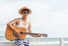 供以人员弹在海滩的一把声学吉他 免版税库存图片