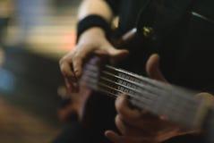 供以人员弹在音乐会阶段的低音吉他弹奏者电子吉他 免版税库存图片