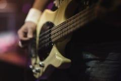 供以人员弹在音乐会阶段的低音吉他弹奏者电子吉他 免版税库存照片