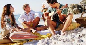 供以人员弹朋友的吉他坐海滩4k 股票录像