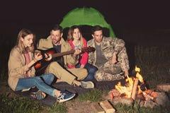 供以人员弹朋友的吉他靠近篝火在晚上 野营的季节 库存图片