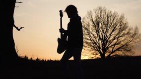 供以人员戏剧电吉他并且唱在领域的一首抒情歌歌曲靠近树在日落 剪影 影视素材