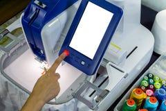 供以人员手按在刺绣机器的` s红色起动buttom 免版税库存照片