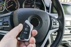 供以人员把握在黑皮革内部的` s手一个无线汽车关键 现代汽车内部细节 汽车详述 里面汽车 汽车det 库存图片