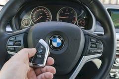 供以人员把握在黑皮革汽车内部的` s手一个无线BMW X5 F15汽车关键 现代汽车内部细节 汽车详述 汽车 免版税库存照片